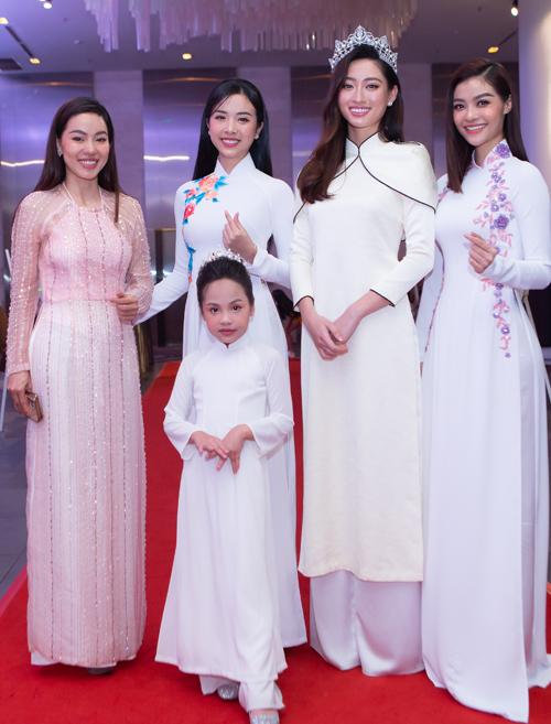 Bà trùm hoa hậu Kim Dung (ngoài cùng bên trái) và á hậu Thúy An (thứ hai từ trái qua) chụp ảnh cùng Lương Thùy Linh, Kiều Loan và bé Hiểu Anh trên thảm đỏ.