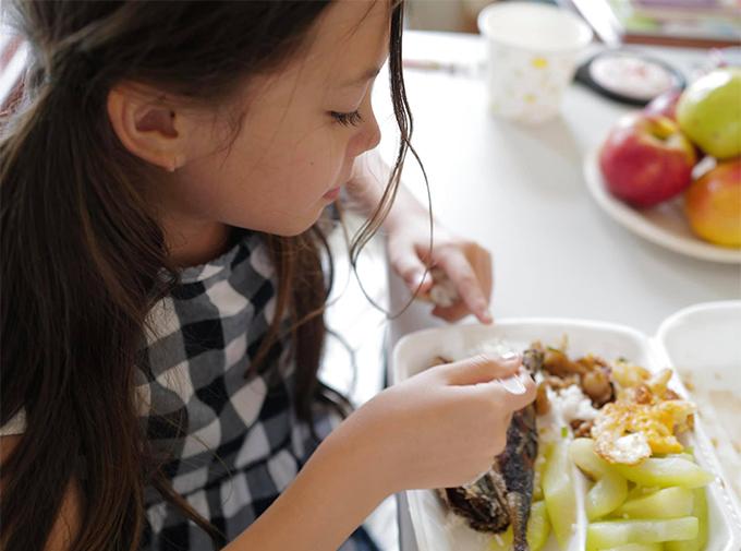 Bé Tép ăn ngon lành suất cơm được phát cho 3 mẹ con ở khu cách ly tập trung.