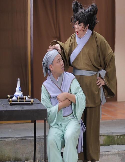 Nghệ sĩ Gia Bảo (đứng) sắm vai bà chủ quán rượu còn diễn viên Lạc Hoàng Long (ngồi) hóa thân con trai chủ quán. Cả hai chọc cười khán giả với những câu nói hài hước, duyên dáng.