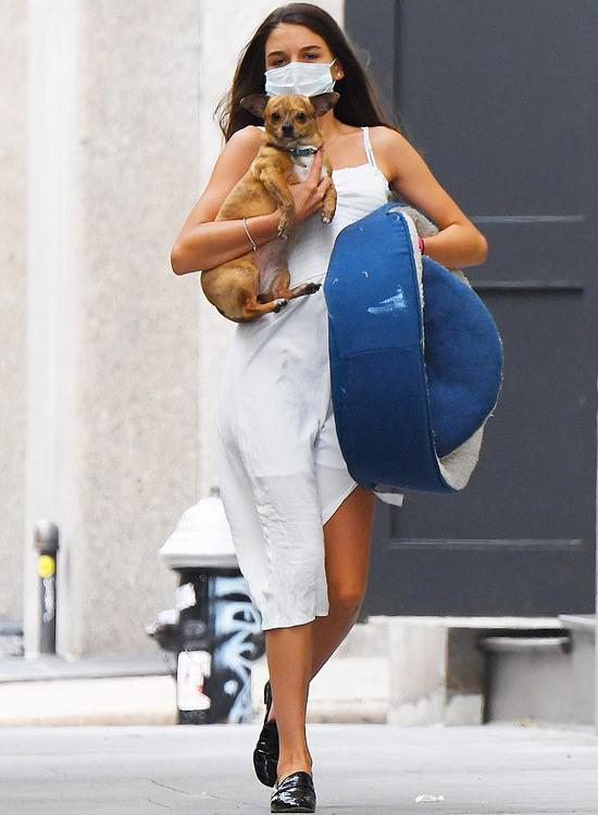 Suri Cruise được trông thấy bế chú cún đi dạo trên đường phố New York hôm 31/7. Cô bé mặc váy hai dây, xỏ giầy da, không còn dấu vết của một nhóc tỳ bé bỏng.