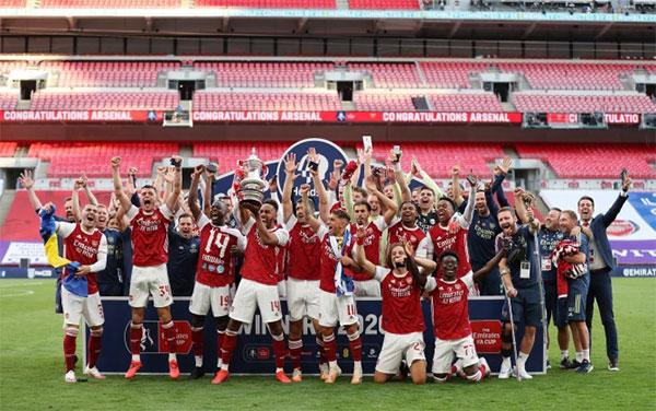 Aubameyang một tay cầm Cup, một tay nâng đế trong lễ mừng vô địch FA Cup. Ảnh: Reuters.