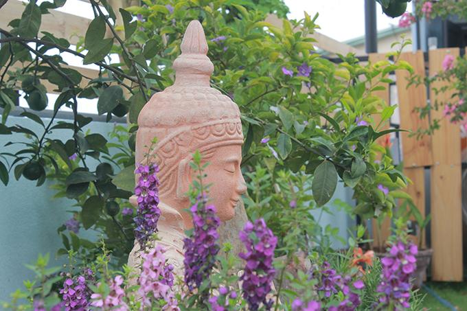Hoa nở khắp vườn sân thượng, nơi đây còn được đặt tượng tạo nên góc riêng giúp gia chủ thiền tịnh, tĩnh tâm.