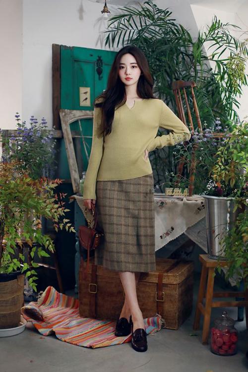 Áo dệt kim mỏng có khả năng giữ nhiệt vừa đủ và dễ phối với các kiểu chân váy midi, đầm suông hoạ tiết ca rô.