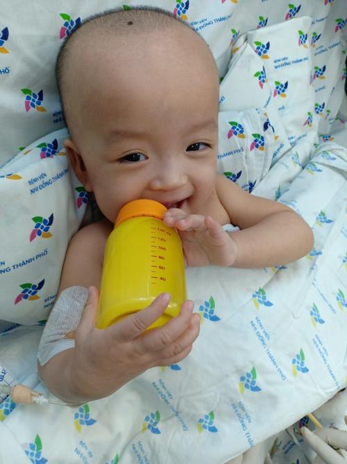Diệu Nhi cầm bình sữa tự uống. Ảnh: Nguyễn Lan Anh.