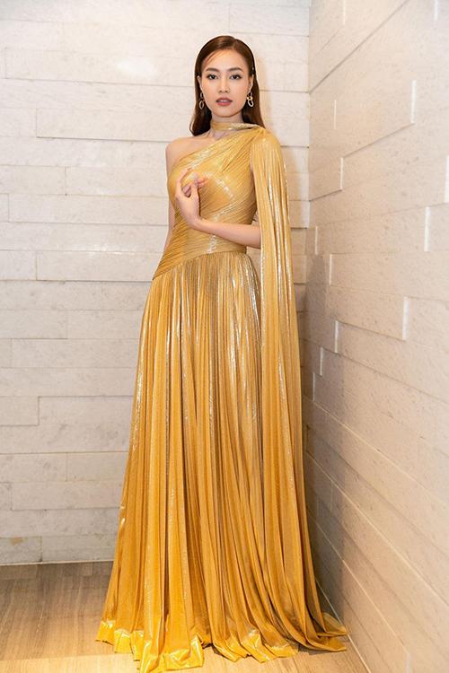Váy bất đối xứng với phần vai choàng nhẹ nhàng lấy cảm hứng từ phong cách nữ thần Hy Lạp giúp người mặc trở nên duyên dáng hơn.