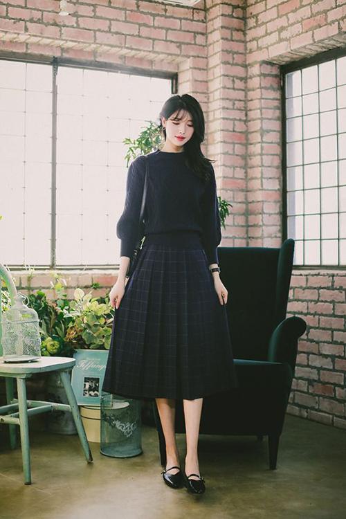Đầm midi vải ca rô được trang trí đường xếp nếp tinh tế giúp thời trang văn phòng trở nên cuốn hút hơn.