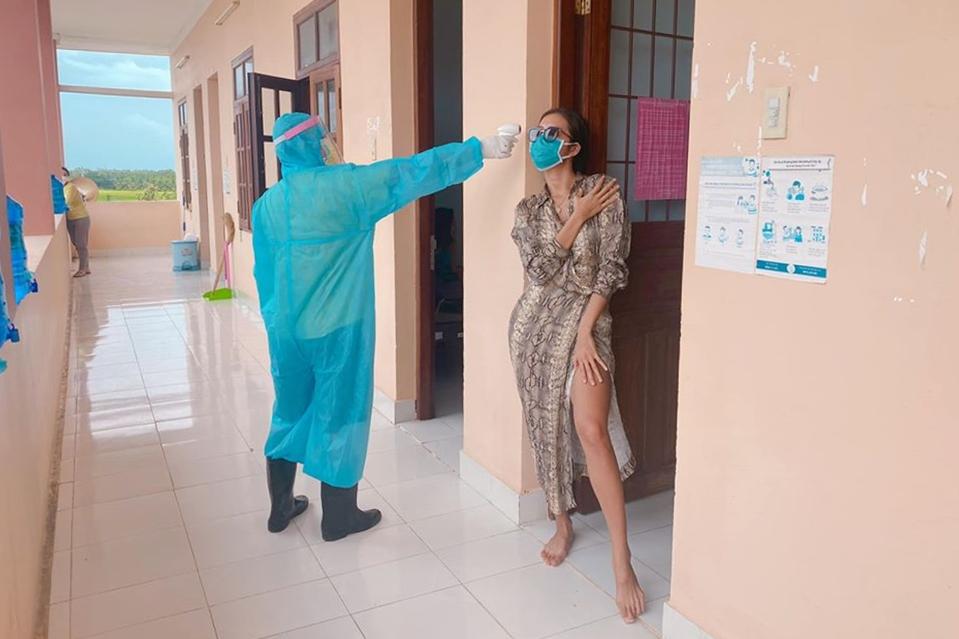 Mỗi ngày, Minh Tú và các công dân khác sẽ được đo nhiệt độ hai lần. Cô dí dỏm vừa đo nhiệt độ vừa tạo dáng thời trang để bạn cùng phòng chụp ảnh kỷ niệm. Chân dài cũng trải qua đợt xét nghiệm nCoV đầu tiên và có kết quả âm tính.