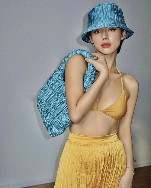Áo tắm tông vàng mùa tạt được Khánh Linh mix ton-sur-ton cùng quần lụa nhăn khi khoe hai mẫu phụ kiện túi xách và mũ mới.