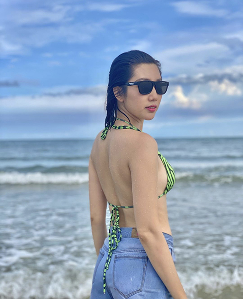 Thuý Ngân sử dụng short jeans lưng cao cùng áo bơi để thoải mái hơn khi vui chơi cùng bạn bè trên bãi biển.