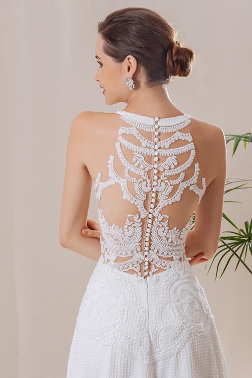 Với NTK Trương Thanh Hải, mặt lưng áo cưới luôn là một bài toán thú vị, có những ẩn số cần anh tìm lời giải. Anh cho rằng một tấm áo cưới đẹp nghĩa là không chỉ có phần thân trước hoàn mỹ mà còn cần đến mặt lưng là một bố cục đầy đủ, có những chi tiết đắt giá để cô dâu níu giữ ánh nhìn của chú rể, khách mời. Ở các tác phẩm áo cưới của mình, anh đều chọn illusion back - lưng váy xuyên thấu, một xu hướng thiết kế phổ biến ở thời trang cưới. Trương Thanh Hải thoả sức tạo hình, thể hiện chi tiết đính kết, hoa văn ren, đá pha lê, nút... trên lớp lưới xuyên thấu, tạo nên một bức tranh hoạ tiết cầu kỳ mặt lưng váy. Lấy ý tưởng từ dáng áo yếm truyền thống, mặt lưng áo trở nên hiện đại hơn cùng những mảng ren thêu tay xếp đăng đối trên lớp lưới tulle xuyên thấu. NTK cùng cộng sự đính kết cườm và đá pha lê lên trên bề mặt của hoạ tiết, làm cho chiếc váy bắt mắt và đắt giá hơn.