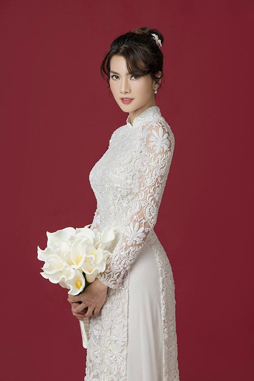 Áo dài không chỉ là trang phục mà còn giúp cô dâu thể hiện cá tính, gu thẩm mỹ của bản thân. Mẫu áo có hoa ren phương Tây được kết hạt để làm tăng hiệu quả bắt sáng.