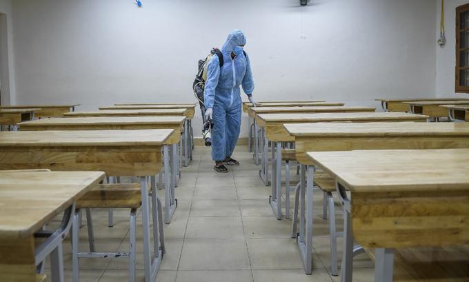 Nhân viên y tế phun khử trùng một điểm thi ở Hà Nội, trước kỳ thi tốt nghiệp THPT diễn ra. Ảnh: Phạm Chiểu.