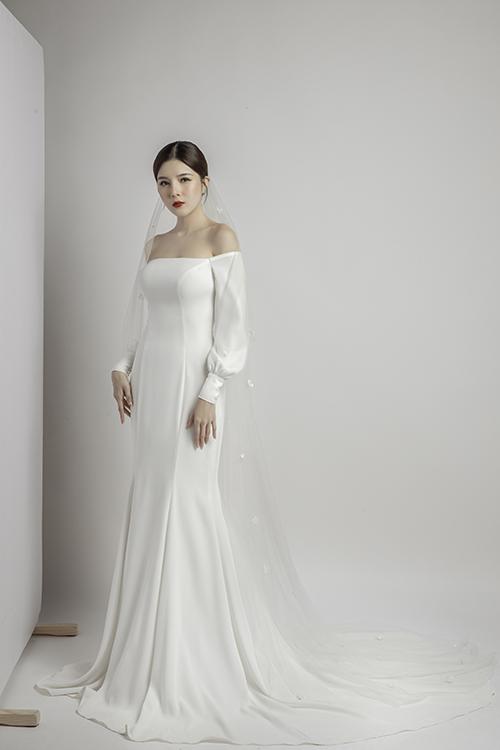 Váy đuôi cá xoè nhẹ cúp ngực, tay phồng không sử dụng tới hoạ tiết mà chỉ dùng đến những đường cắt may tinh tế để làm nổi vóc dáng của cô dâu.