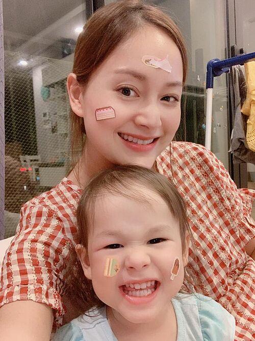 Con gái Lan Phương khoái chí khi được dán sticker lên mặt và lí lắc pose hình.