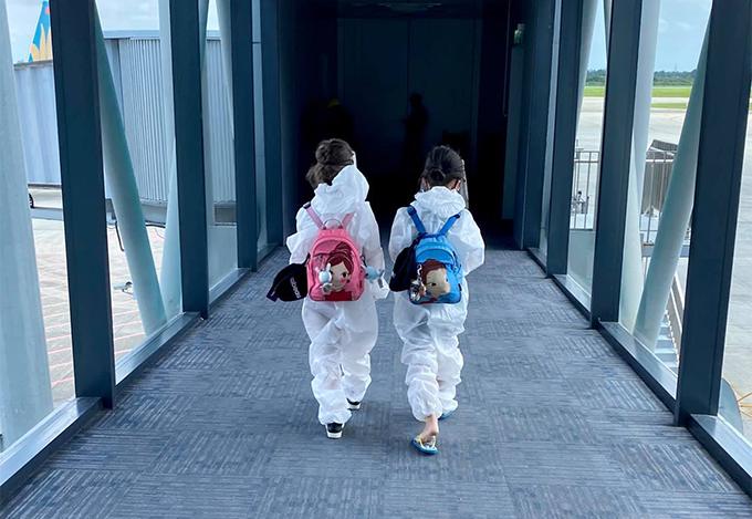 Tôm và Tép mặc đồ bảo hộ khi lên máy bay về TP HCM.
