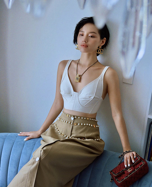 Diện áo crop-top khoe nét gợi cảm cùng chân váy màu trung tính, Khánh Linh sử dụng túi đỏ đậm để tạo điểm nhấn cho set đồ.