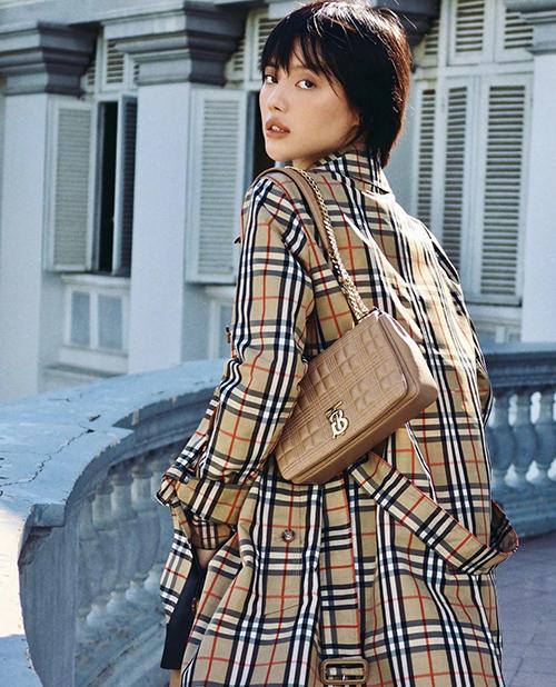 Người đẹp chọn túi màu cafe sữa để tạo nên sự đồng điệu với áo choàng hoạ tiết kẻ sọc ca rô quen thuộc của thương hiệu Burberry.