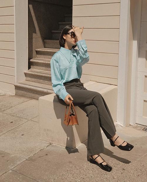 Sơ mi cổ điển với tông xanh nhẹ nhàng có thể mix cùng các mẫu quần suông ống đứng, quần lưng cao để chưng diện chốn công sở.
