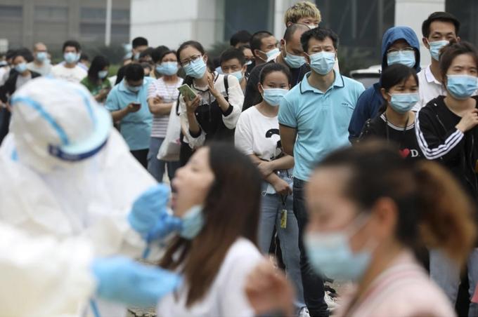 Người dân được kiểm tra sức khỏe tại một điểm kiểm dịch ở Hồ Bắc,Trung Quốc.Ảnh: AP.