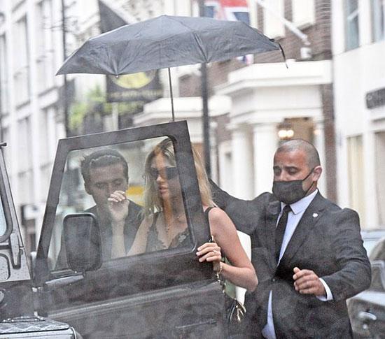 Chàng trai nhà Becks ga lăng mở cửa xe cho vợ sắp cưới vào trước trong khi một vệ sĩ đi phía sau che ô cho người đẹp.