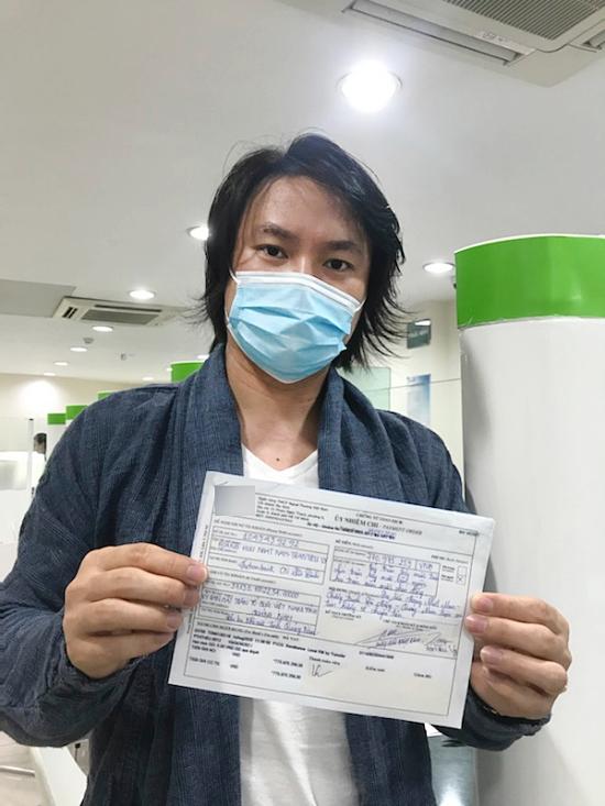 Đạo diễn Hoàng Nhật Nam tại ngân hàng để chuyển khoản tiền ủng hộ đến Đà Nẵng.