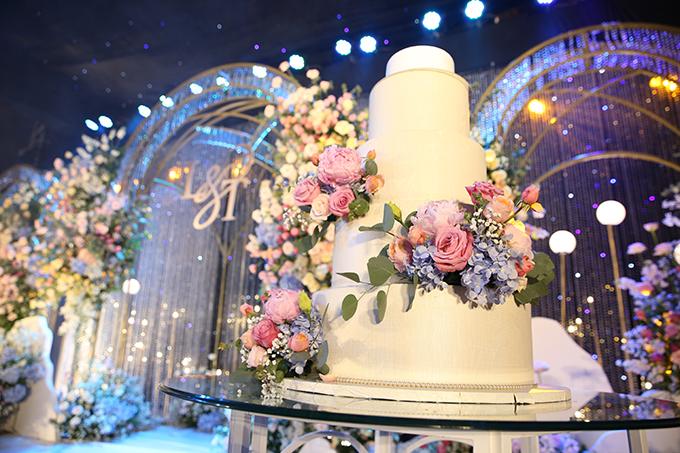 Bánh cưới của uyên ương có tông trắng, được điểm xuyết hoa tươi.