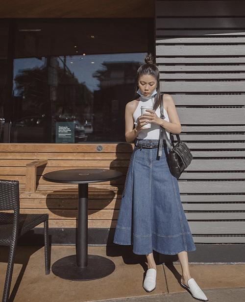Chân váy jeans dáng dài phối cùng áo thun ba lỗ vẫn có thể chưng dụng trong những ngày đầu thu. Phối cùng set đồ này, các nàng có thể chọn giày mullet, túi đeo chéo, túi da đan để mix đồ.