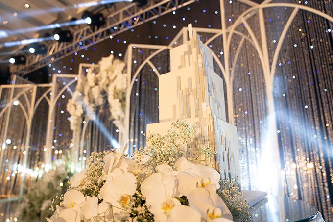 Bánh cưới cao cấp được tạo hình khối vuông 3 tầng với hoạ tiết mô phỏng kim loại, trang trí bởi hoa lan bên dưới.