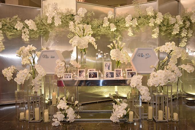 Bàn gallery được tinh giản với các khối pha lê trong suốt, được thắp nến bên trong và hoa lan trắng muốt.