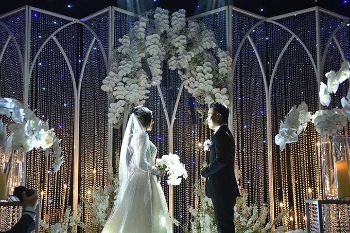 Khu vực backdrop trên sân khấu làm từ các sợi pha lê, hoa tươi được gắn thủ công. Từng viên pha lê cao cấp được mài giũa kỹ càng từng góc cạnh, đảm bảo độ bắt sáng tốt.