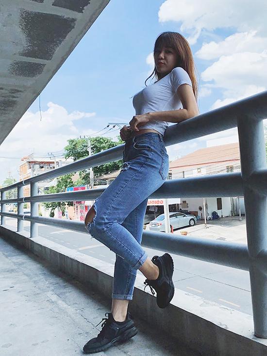 Mặc quần jeans rách năng động, cô không quên chọn dáng đứng giúp  đường cong thêm nổi bật.