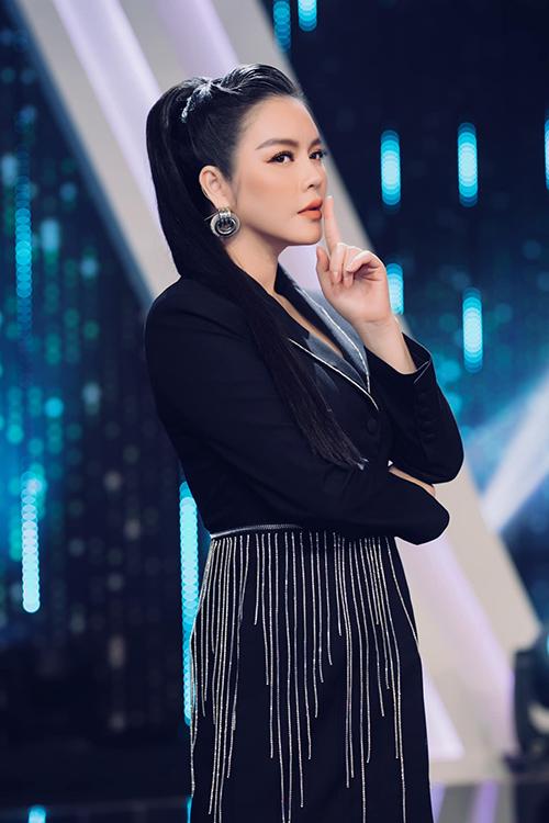 Váy vest tông đen được trang trí đường viền màu tương phản, đồng thời phần eo còn được tô điểm bằng vạt đá trắng lấp lánh.