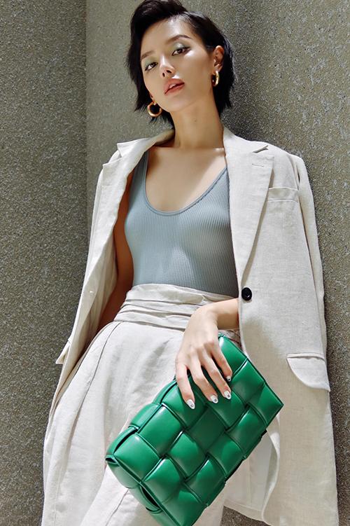 Diện suit màu trắng kem theo phong cách thanh lịch, Khánh Linh chọn thêm clutch da đan màu xanh lá để tạo điểm nhấn cho set đồ.