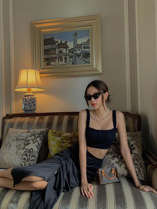 Chân váy xẻ tà với đường nhún độc đáo được Phí Phương Anh mix đồng điệu với áo hở eo. Phụ kiện đi kèm là túi bé xinh của Louis Vuitton.