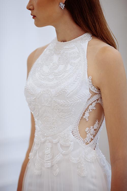 Váy cưới mang tên Hypatia được lấy cảm hứng từ áo yếm, cách tân hiện đại với chi tiết đính kết bằng ren, pha lê trong suốt. Dáng váy suông được phủ thêm lớp lưới trắng xoè sát đất, giúp tạo hiệu ứng làn váy tung bay trong gió.