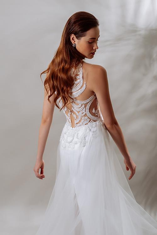 Thân sau váy được trang trí với ren, pha lê đồng điệu với thân trước trên nền vải lưới xuyên thấu. Đường vạt xẻ giúp cô dâu di chuyển dễ dàng.