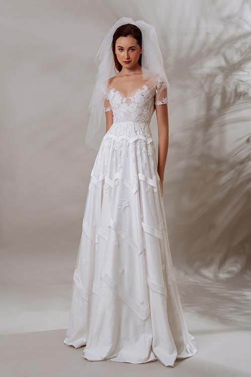 Mẫu đầm Lilyn có cách phối ghép vải cầu kỳ, đòi hỏi kỹ thuật rập, rã vải phức tạp. Thân áo xếp nếp cùng nhiều lớp vải nền hoa ren bên trong.