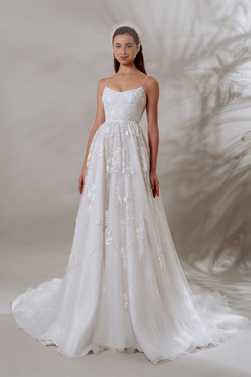 Váy Emma có phom xoè nhẹ, ren hoa đính dọc thân. Vai áo tôn vẻ gợi cảm nhờ thiết kế cúp ngực, sợi dây mảnh.