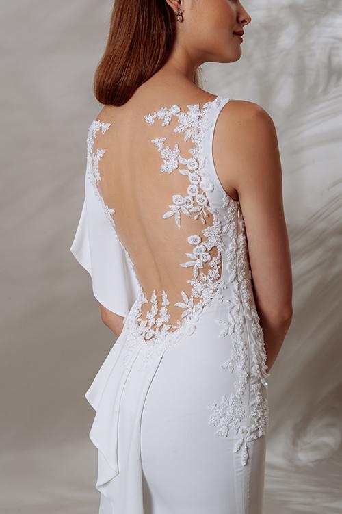 Mặt lưng váy có hoạ tiết hoa thêu, đắp vạt bèo xếp nếp một bên. Thân váy xẻ bên dưới giúp cô dâu dễ di chuyển.