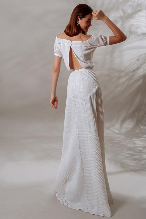 Lưng váy có khoảng hở nhờ đường xẻ ở giữa, được nối lại bằng nút bọc.