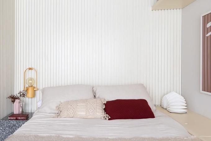 Giường ngủ mang tông màu trung tính. Bên cạnh phía tay trái  là kệ gỗ để đựng đồ. Kệ được kéo dài tới phía cuối giường để làm kệ đựng sách.