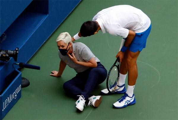 Djokovic thăm hỏi trọng tài dây sau sự cố. Ảnh: EPA.