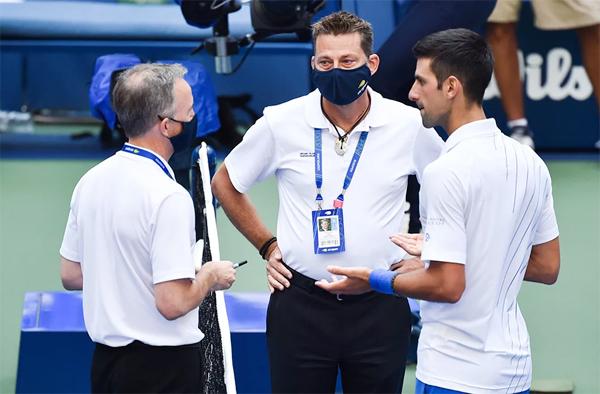 Djokovic giải thích với trọng tài và các giám sát về tình huống vô tình đánh bóng vào trọng tài đây trong trận đấu vòng 4. Ảnh: The Sun.