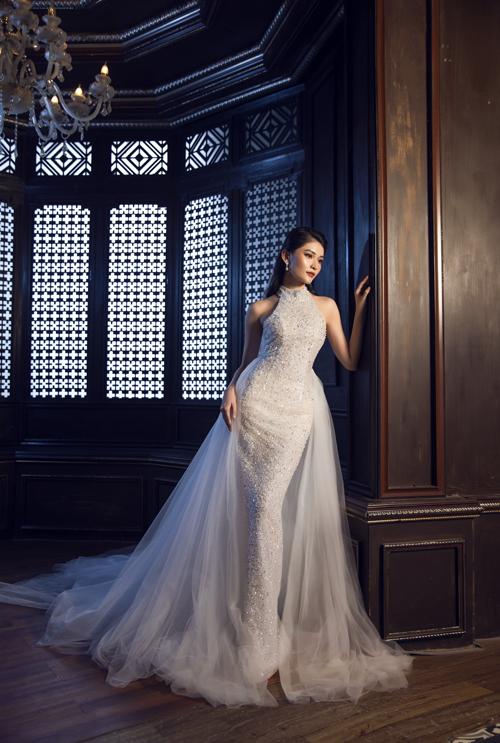 Bộ cánh điểm hạt dọc thân, tạo hiệu ứng sân khấu tối đa cho cô dâu. Váy đuôi cá có voan dài đính nơi hông, tạo sự thướt tha cho cô dâu khi di chuyển.