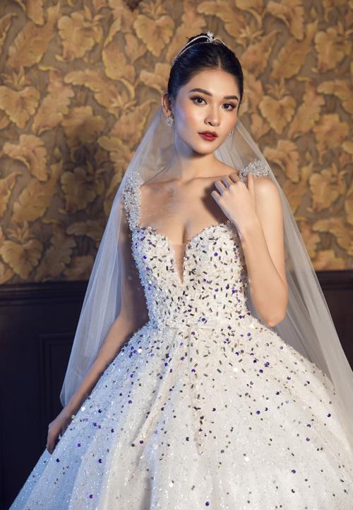 Đầm cưới mang sắc màu cổ tích với hạt đá lấp lánh sắc xanh trên nền vải trắng.
