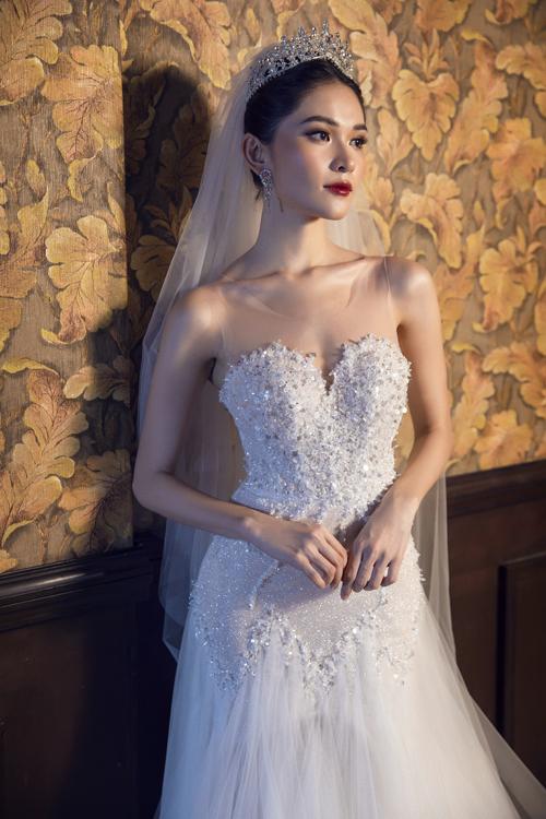 Đầm ôm cách điệu với cúp ngực cổ tim, họa tiết trái tim nơi thân váy là lựa chọn của cô dâu yêu thích sự trẻ trung, năng động.