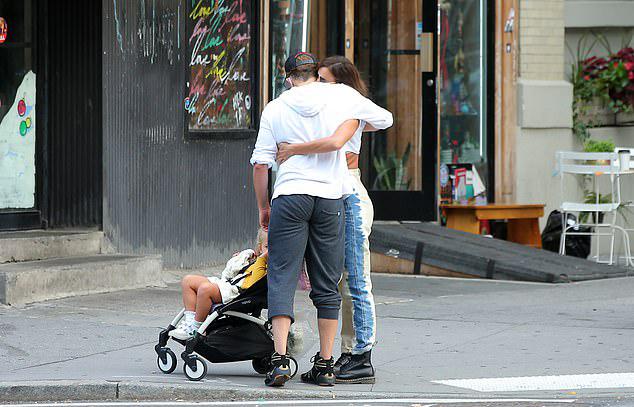Cô con gái Lea 3 tuổi ngồi đợi trên xe đẩy, nhìn bố mẹ thể hiện tình cảm.