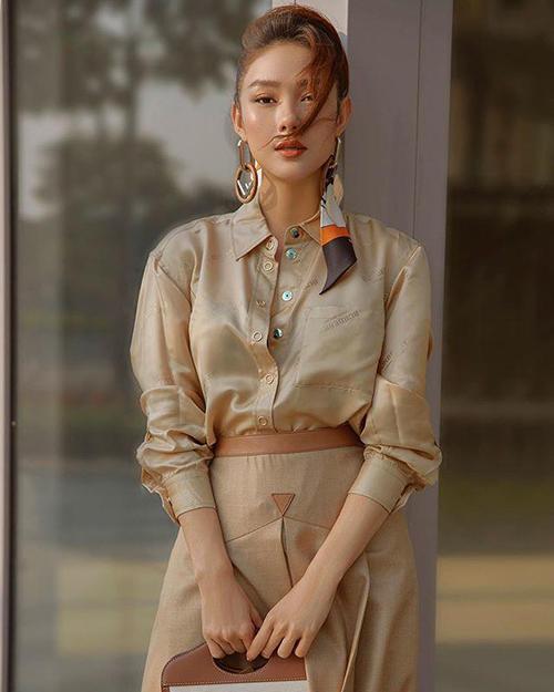 Minh Hằng mix trang phục ton-sur-ton với gam nâu nhẹ nhàng cho sơ mi, chân váy và túi hiệu của Burberry.