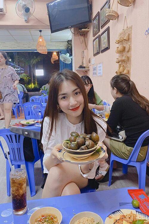 Hòa Minzy mặc giản dị, thưởng thức ốc ở quán bình dân.