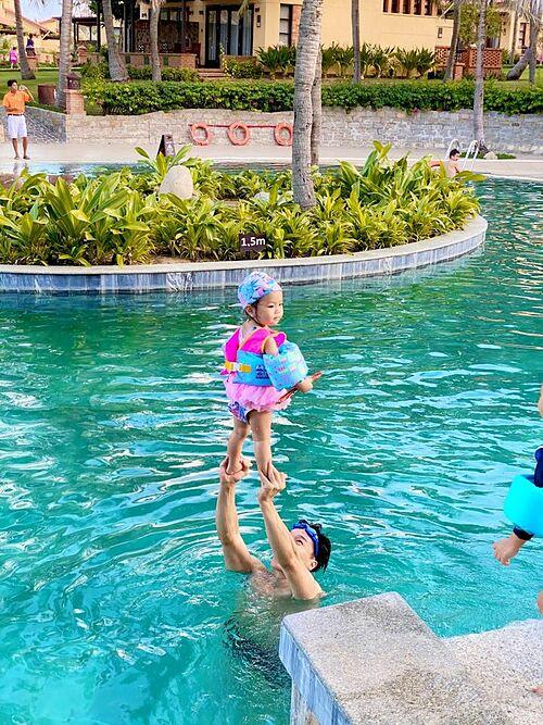 Quốc Nghiệp và con gái làm xiếc trong hồ bơi.
